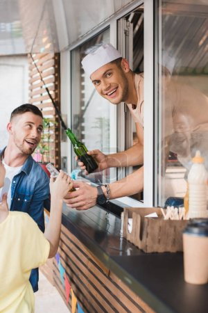 smiling chef giving drinks to customers from food truck and looking at camera