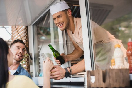 smiling chef giving drinks to customers from food truck