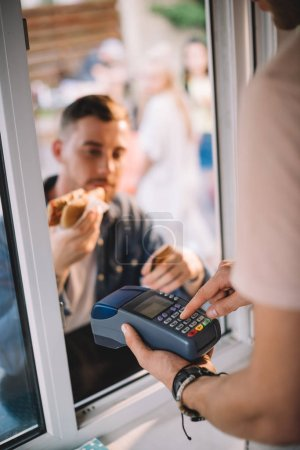 selective focus of customer paying for hot dog in food truck