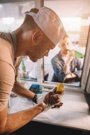 chef preparing hod dog in food truck