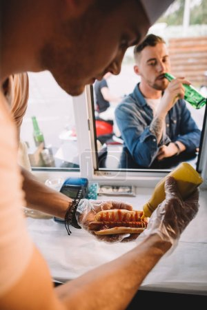 chef preparing hod dog in food truck, customer drinking beer