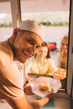 smiling chef giving burger and french fries to customers from food truck