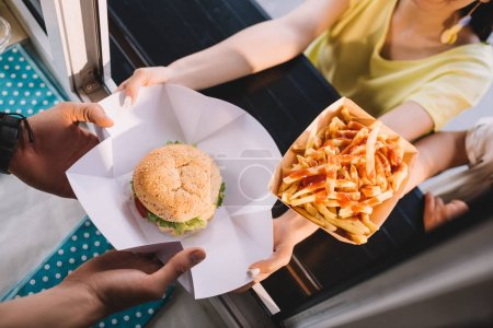 cropped image of chef giving burger and french fries to customers from food truck