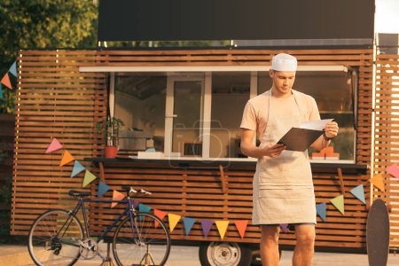 handsome chef in apron looking at clipboard near food truck