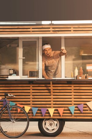 smiling chef gesturing and calling someone from food truck