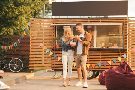 smiling couple holding french fries and burger near food truck