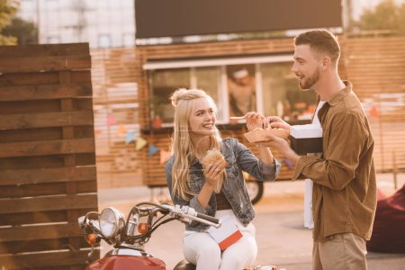 young couple eating french fries and burger near food truck