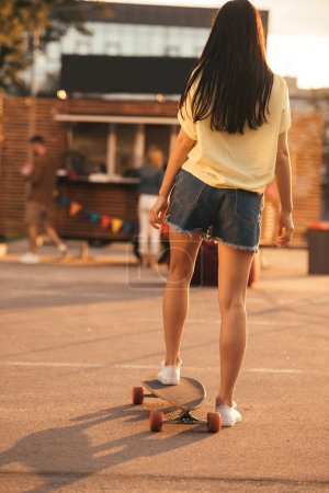 rear view of girl standing on skateboard near food truck