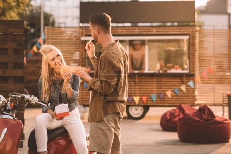 happy couple eating french fries and burger near food truck