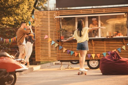 back view of girl standing on skateboard near food truck