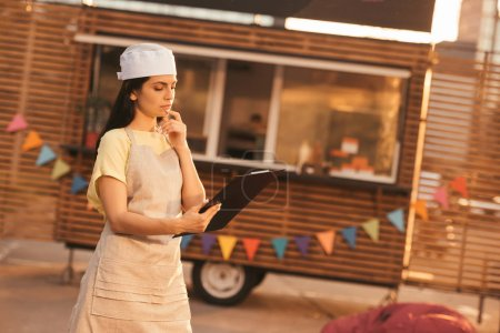 attractive pensive chef in apron holding clipboard near food truck