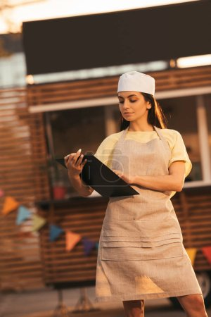 attractive chef in apron holding clipboard near food truck