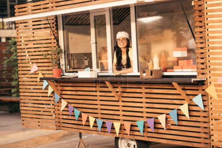 smiling attractive chef looking at camera from food truck