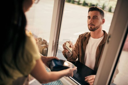 cropped image of handsome customer paying with credit card for food at food truck