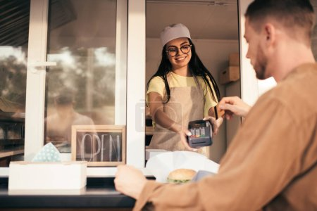 customer paying with credit card for food at food truck