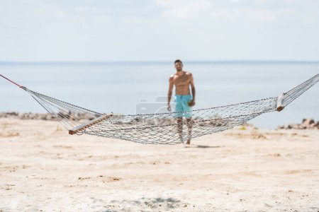 selective focus of hammock and shirtless man walking on beach on background