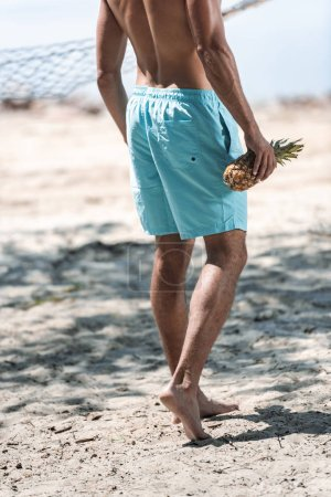 cropped view of man holding fresh pineapple on beach