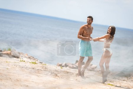 beautiful couple holding hands and having fun on beach