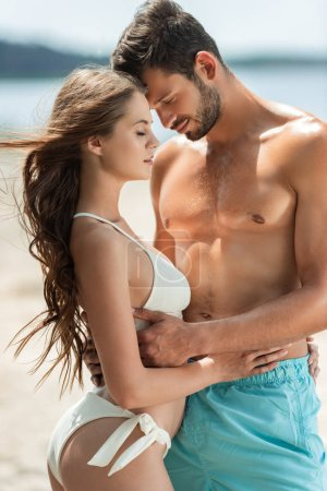 Photo for Beautiful couple with closed eyes hugging on beach - Royalty Free Image