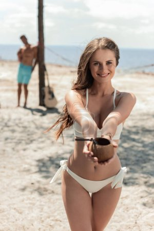 beautiful young woman holding coconut cocktail on beach with boyfriend on background