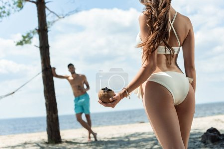 girl with coconut cocktail looking her boyfriend on seashore, selective focus
