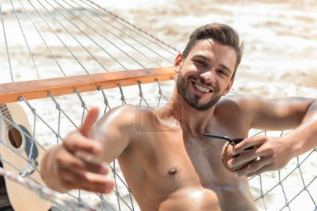 handsome smiling man relaxing with coconut cocktail in hammock