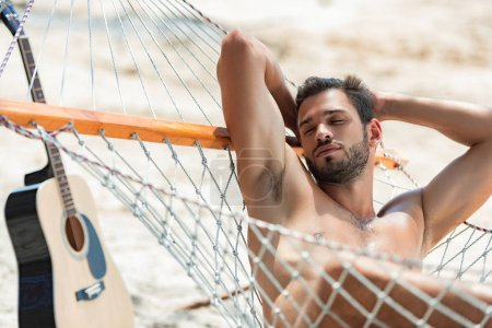 Photo for Handsome bearded man relaxing in hammock - Royalty Free Image
