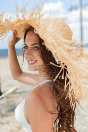 cheerful attractive girl posing in straw hat in summer