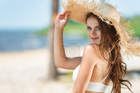 beautiful girl posing in swimsuit and straw hat on beach