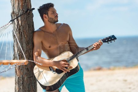 male shirtless musician playing acoustic guitar on beach