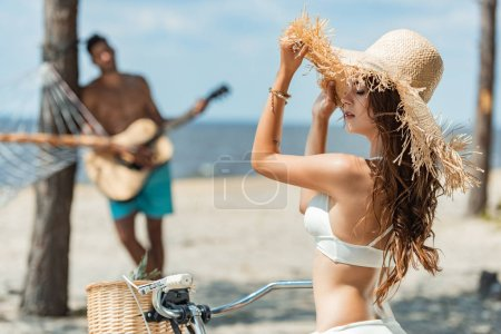 beautiful girl in straw hat with bike and boyfriend with acoustic guitar on seashore, selective focus