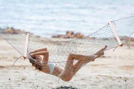 beautiful young woman in bikini resting on hammock on beach