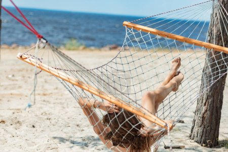 attractive girl relaxing in hammock on beach