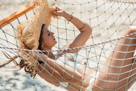 Photo for Attractive girl in swimsuit and straw hat resting in hammock on beach - Royalty Free Image