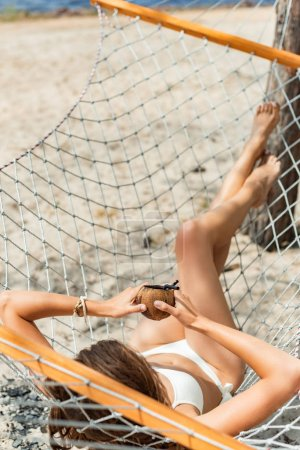 young woman in bikini holding coconut cocktail and lying in hammock on beach