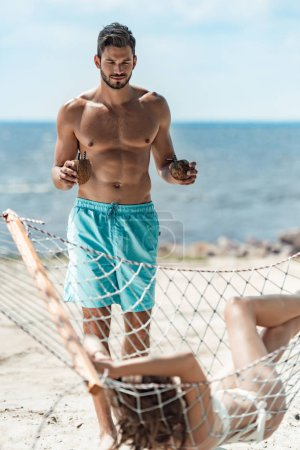 Photo for Shirtless boyfriend bringing coconut cocktails to his beautiful girlfriend on hammock, selective focus - Royalty Free Image