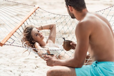 Photo for Boyfriend bringing coconut cocktails to his beautiful girlfriend on hammock - Royalty Free Image