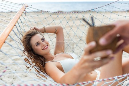 selective focus of man giving coconut cocktail to his attractive girlfriend on hammock