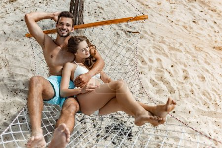 happy young couple relaxing on hammock on beach