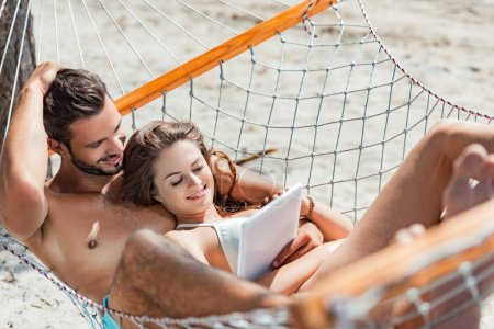 smiling couple using digital tablet while relaxing on hammock on beach