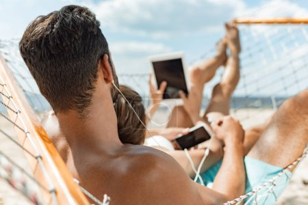 young couple listening music with earphones and gadgets while relaxing on hammock on beach
