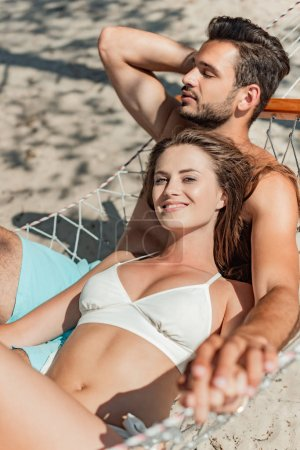 Photo for Smiling couple of tourists relaxing in hammock on sandy beach - Royalty Free Image