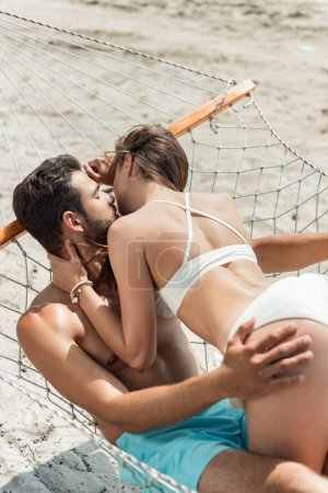 young couple of lovers kissing and relaxing in hammock on beach