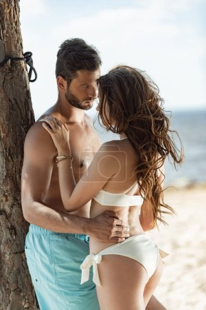 Photo for Beautiful couple hugging near tree on beach in summer - Royalty Free Image