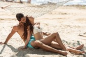 couple of tourists relaxing on sandy beach near hammock