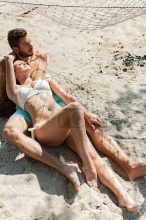 happy beautiful couple lying on sandy beach