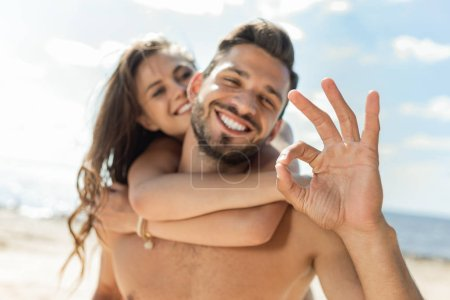 selective focus of man showing ok sign and piggybacking his girlfriend