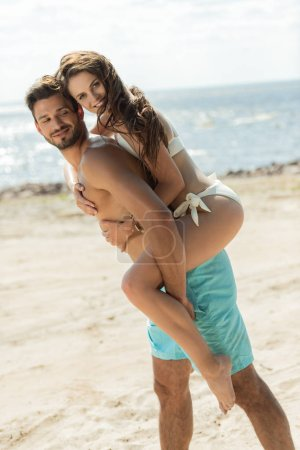 young man piggybacking his girlfriend on sandy beach near the sea