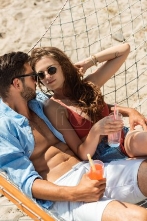 beautiful young couple in sunglasses relaxing in hammock with cocktails