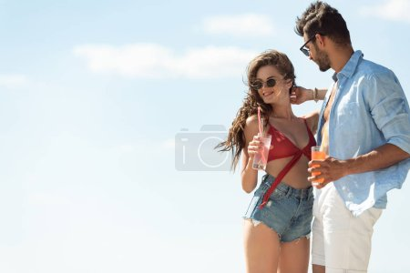 Photo for Beautiful couple embracing and holding alcohol cocktails, blue sky on background - Royalty Free Image